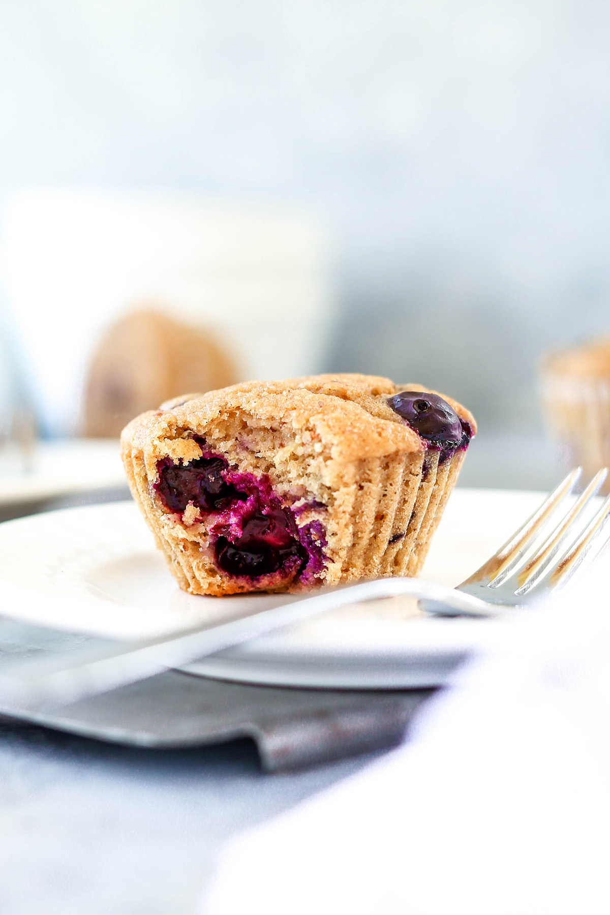a blueberry apple muffin on a plate with a fork